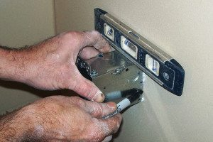 1 - Hold the outlet box against the drywall with a short level on the top