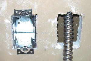 6 - A helper locates the end of the conduit and pulls it though the open outlet hole