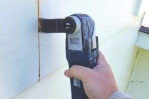 An oscillating multi tool was used to cut out damaged sections to repair wood siding